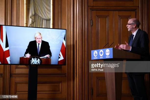 Britain's Prime Minister Boris Johnson and Director of the Oxford Vaccine Group Andrew Pollard attend a virtual news conference on the ongoing...