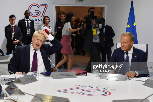 Britain's Prime Minister Boris Johnson and European Council President Donald Tusk meet for the first working session of the G7 Summit on August 25,...