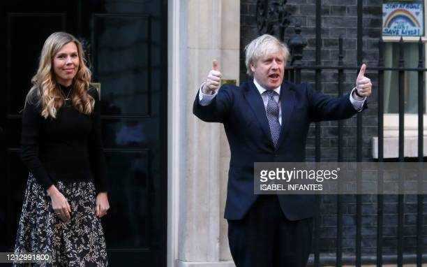 Britain's Prime Minister Boris Johnson and his fiancee Carrie Symonds participate in a national clap for carers to show thanks for the work of...