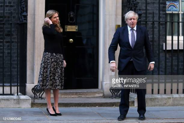 "Britain's Prime Minister Boris Johnson and his fiancee Carrie Symonds participate in a national ""clap for carers"" to show thanks for the work of..."