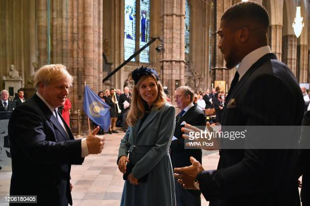 Britain's Prime Minister Boris Johnson and his fiancee partner Carrie Symonds talk with British boxer Anthony Joshua as they leave after attending...