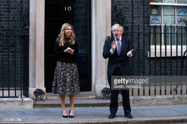 "Britain's Prime Minister Boris Johnson and his finacee Carrie Symonds participate in a national ""clap for carers"" to show thanks for the work of..."