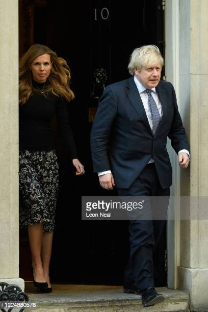 Britain's Prime Minister Boris Johnson and his partner Carrie Symonds stand outside the door of number 10 Downing Street as they thank the key...
