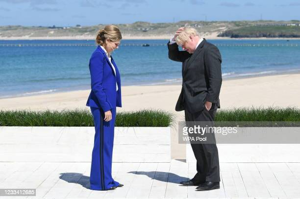 Britain's Prime Minister Boris Johnson and his spouse Carrie Johnson wait to greet guests at an official welcome at the G7 summit in Carbis Bay on...