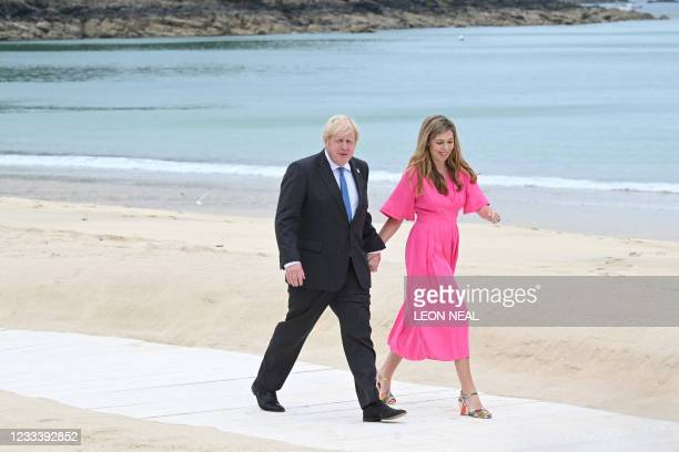 Britain's Prime Minister Boris Johnson and his wife Carrie Johnson arrive on the beach to greet guests at the start of the G7 summit in Carbis Bay,...
