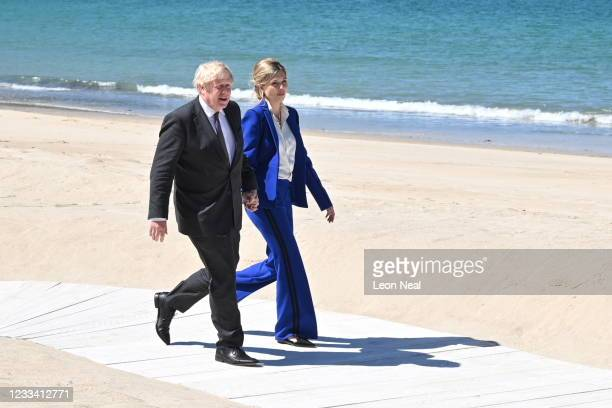 Britain's Prime Minister Boris Johnson and his wife Carrie Johnson make their way to greet guests at an official welcome at the G7 summit in Carbis...