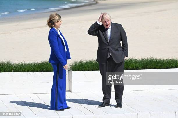 Britain's Prime Minister Boris Johnson and his wife Carrie Johnson wait to greet guests at an official welcome at the G7 summit in Carbis Bay on June...