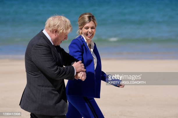 Britain's Prime Minister Boris Johnson and his wife Carrie Johnson arrive to welcome leaders during the G7 summit in Carbis Bay, Cornwall on June 12,...