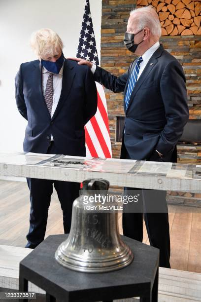 Britain's Prime Minister Boris Johnson and US President Joe Biden, wearing face coverings due to Covid-19, view documents relating to the Atlantic...
