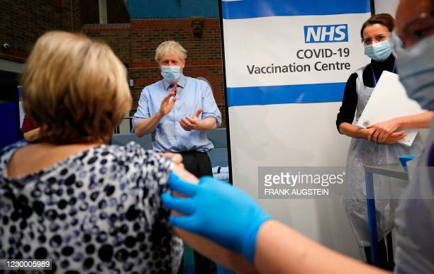 Britain's Prime Minister Boris Johnson applauds after nurse Rebecca Cathersides administered the Pfizer-BioNTech COVID-19 vaccine to Lyn Wheeler at...