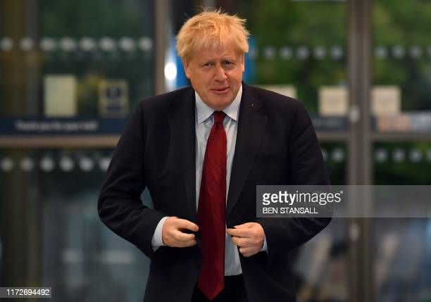 Britain's Prime Minister Boris Johnson arrives at the Manchester Central convention complex to give media interviews ahead of the third day of the...