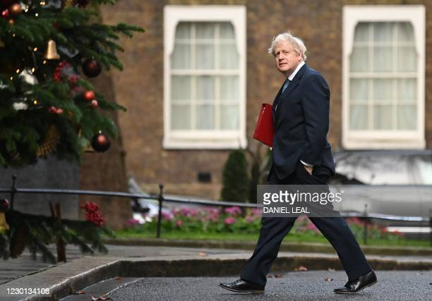 Britain's Prime Minister Boris Johnson arrives back at 10 Downing Street in London on December 15, 2020 after chairing the weekly cabinet meeting...