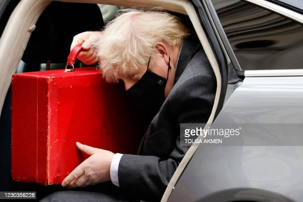 Britain's Prime Minister Boris Johnson arrives back at 10 Downing Street in London on December 30, 2020 after opening the debate on the second...
