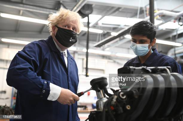 Britain's Prime Minister Boris Johnson assists in an engine repair at the Automotive shop during a visit to Kirklees College Springfield Sixth Form...