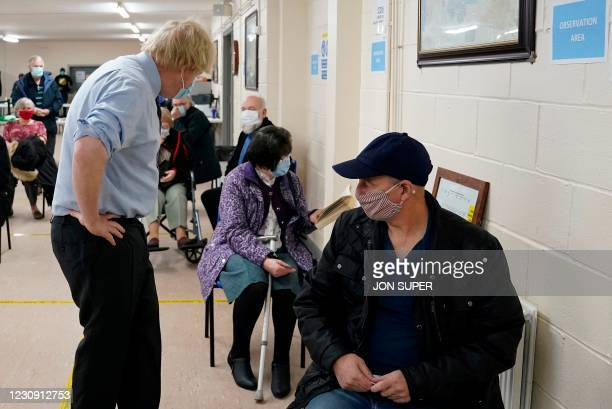 Britain's Prime Minister Boris Johnson attempts to engage with a member of the public waiting to receive their vaccine as he visits a coronavirus...