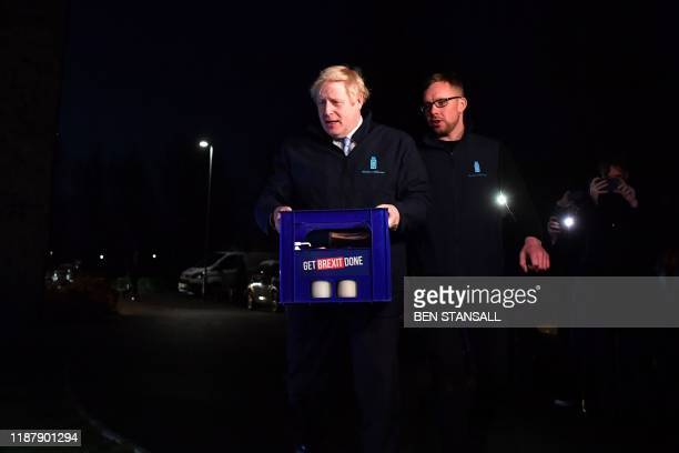 Britain's Prime Minister Boris Johnson carries a crate of milk to deliver to customers in Guiseley Leeds on December 11 2019 on the final day of...