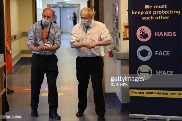 Britain's Prime Minister Boris Johnson cleans his hands with Nick Hulme , Chief Executive as he visits Colchester hospital in Colchester, eastern...