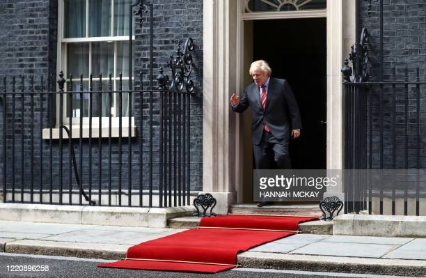 Britain's Prime Minister Boris Johnson comes out to greet French President Emmanuel Macron outside 10 Downing Street in central London on June 18,...