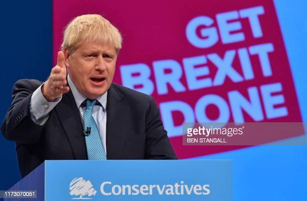TOPSHOT Britain's Prime Minister Boris Johnson delivers his keynote speech to delegates on the final day of the annual Conservative Party conference...