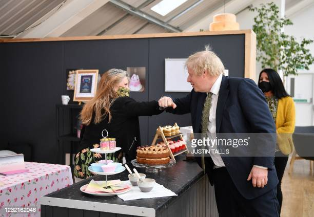 Britain's Prime Minister Boris Johnson elbow bumps a business owner during his visit to Lemon Street Market in Truro, Cornwall, southwest England on...