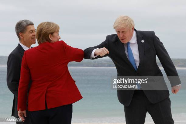 Britain's Prime Minister Boris Johnson elbow-bumps Germany's Chancellor Angela Merkel as he greets her and her husband Joachim Sauer at the G7 summit...