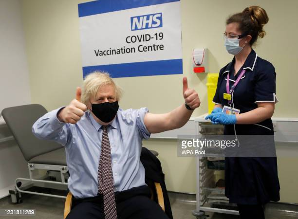 Britain's Prime Minister Boris Johnson gestures after receiving the first dose of AstraZeneca vaccine administered by nurse and Clinical Pod Lead,...