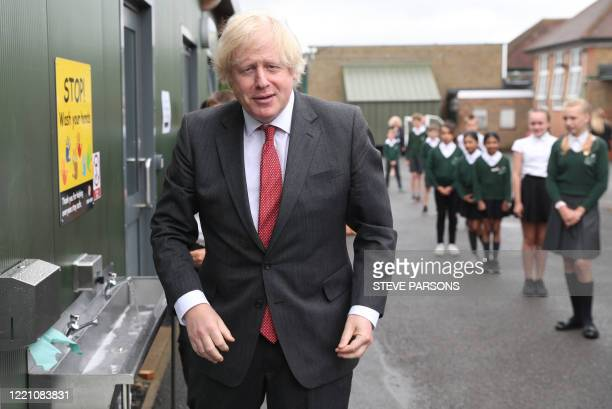 Britain's Prime Minister Boris Johnson gestures after washing his hands at a sink in the playground during a visit to Bovingdon Primary School in...