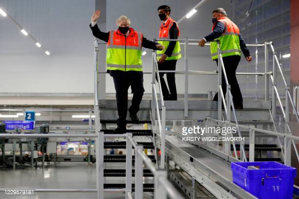 Britain's Prime Minister Boris Johnson gestures as he and Britain's Chancellor of the Exchequer Rishi Sunak are given a tour of a tesco.com...