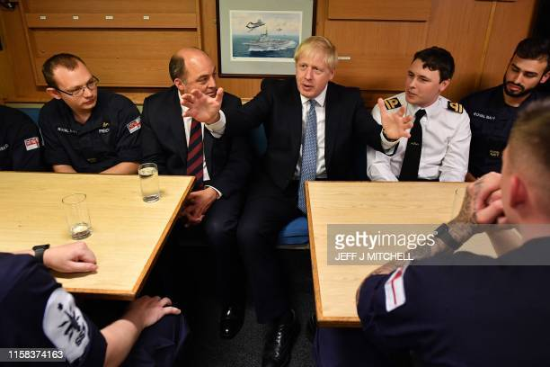 Britain's Prime Minister Boris Johnson gestures as he chats with crew members of Vanguardclass submarine HMS Victorious in the mess hall during a...