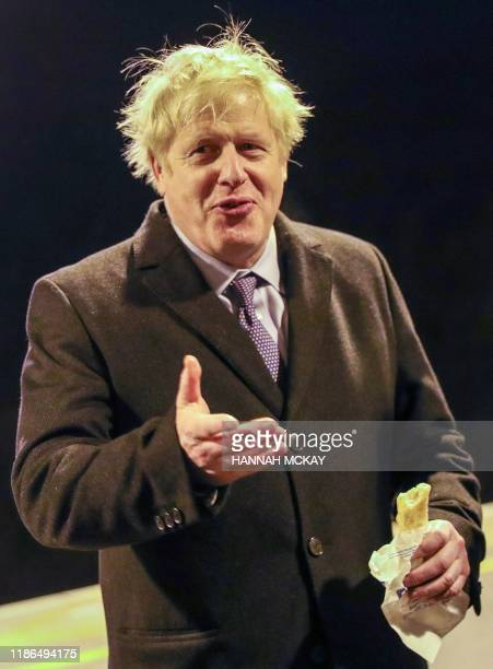 "Britain's Prime Minister Boris Johnson gestures as he holds a ""Greggs"" sausage roll, on the platform of Milton Keynes train station in Milton Keynes,..."