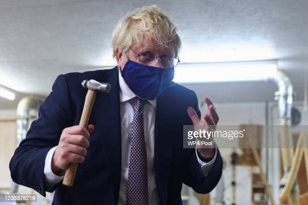 Britain's Prime Minister Boris Johnson gestures as he holds a hammer after hammering a piece of Cornish tin into the model, as he visits the workshop...