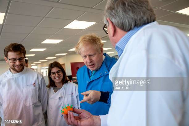 Britain's Prime Minister Boris Johnson gestures as he meets with staff during a visit to the Mologic Laboratory in the Bedford technology Park north...