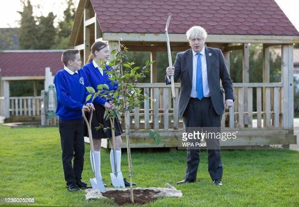 Britain's Prime Minister Boris Johnson gestures as he plants a tree with help from P7 pupils Sophie and Oscar during a visit to Crumlin Intergrated...