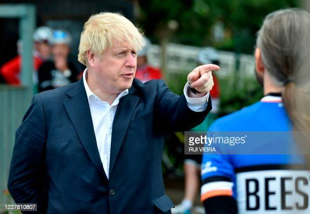 Britain's Prime Minister Boris Johnson gestures as he talks to members of a local cycling club at the Canal Side Heritage Centre in Beeston, central...
