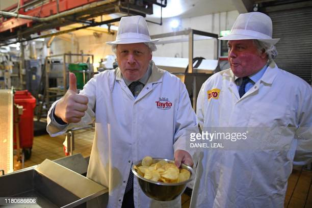 Britain's Prime Minister Boris Johnson gestures besides Tayto Chairman Stephen Hutchinson during a general election campaign visit to the Tayto...