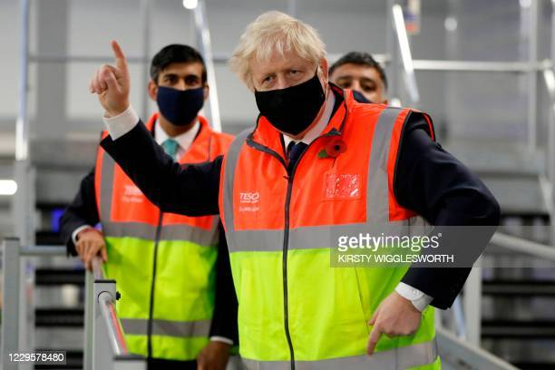 Britain's Prime Minister Boris Johnson gestures during a visit to a tesco.com distribution centre in London with Britain's Chancellor of the...