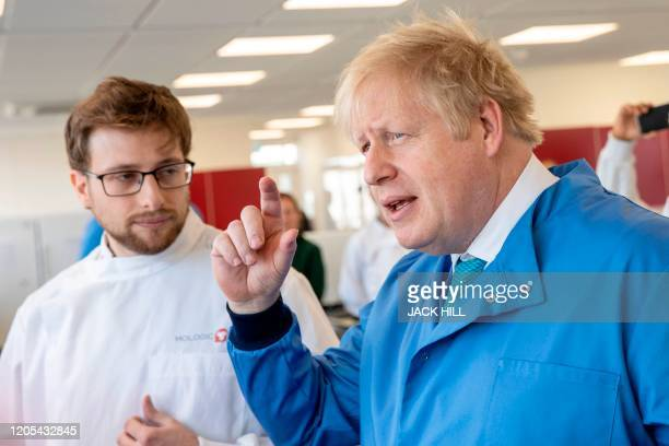 Britain's Prime Minister Boris Johnson gestures during a visit to the Mologic Laboratory in the Bedford technology Park north of London on March 6...