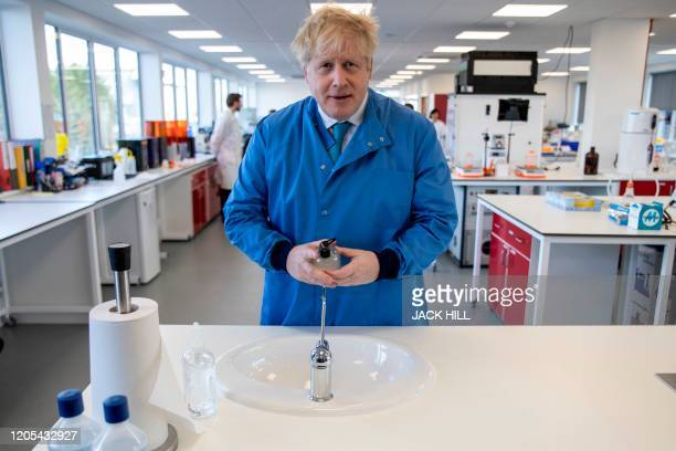 Britain's Prime Minister Boris Johnson gestures during a visit to the Mologic Laboratory in the Bedford technology Park, north of London on March 6,...