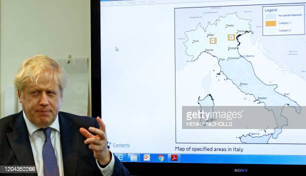 Britain's Prime Minister Boris Johnson gestures in front of a map of Italy in the command centre during a visit to the Public Health England National...