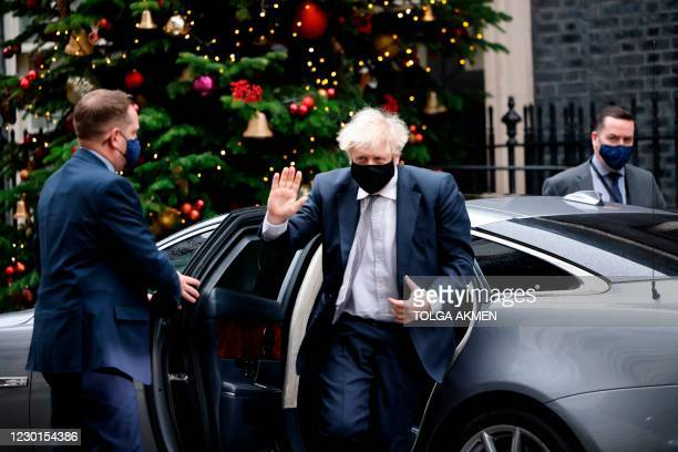 Britain's Prime Minister Boris Johnson gestures on his return to 10 Downing Street in central London on December 16 after taking part in the weekly...