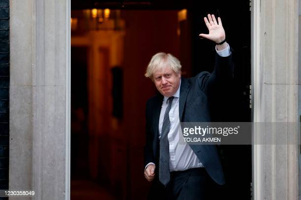 Britain's Prime Minister Boris Johnson gestures to members of the media as he arrives back at 10 Downing Street in London on December 30 after voting...