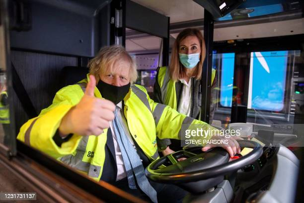 Britain's Prime Minister Boris Johnson gives a thumbs up as he sits in the driver's seat of an electric bus alongside electric vehicles operations...
