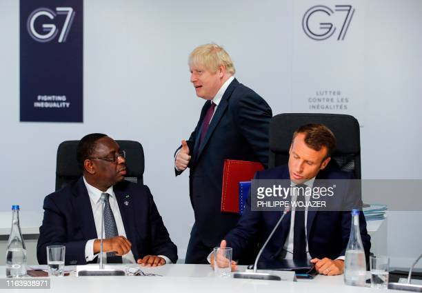 TOPSHOT Britain's Prime Minister Boris Johnson gives a thumbs up as he walks past French President Emmanuel Macron and Senegal's President Macky Sall...