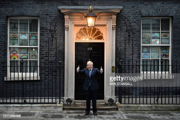 Britain's Prime Minister Boris Johnson gives a thumbs up gesture after participating in a national clap for carers to show thanks for the work of...