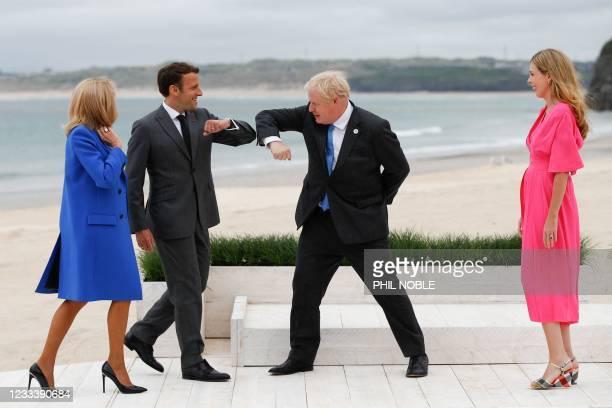 Britain's Prime Minister Boris Johnson greets France's President Emmanuel Macron as their spouses, Carrie Johnson and Brigitte Macron, stand near...