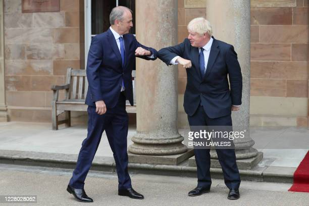 Britain's Prime Minister Boris Johnson greets Ireland's Prime Minister Micheal Martin with an elbow touch as a safety measure because of the novel...