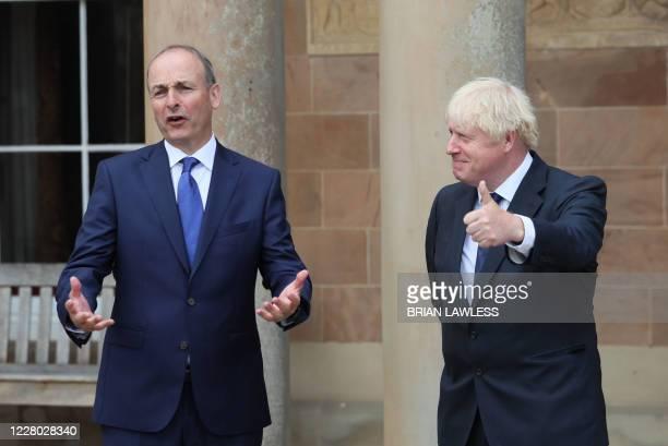 Britain's Prime Minister Boris Johnson greets Ireland's Prime Minister Micheal Martin on the steps of Hillsborough Castle in Belfast on August 13,...