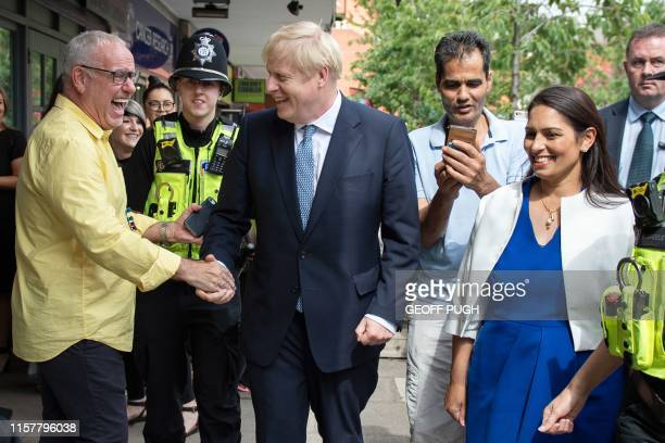 Britain's Prime Minister Boris Johnson greets members of the public on a walkabout with Britain's Home Secretary Priti Patel and members of West...