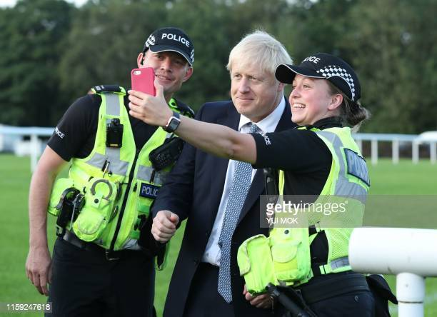 TOPSHOT Britain's Prime Minister Boris Johnson has a selfie taken with police officers as he arrives to meet emergency crews at Whaley Bridge...