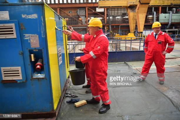 Britain's Prime Minister Boris Johnson helps out with the painting of an electrical generator during his visit to Appledore Shipyard in south west...